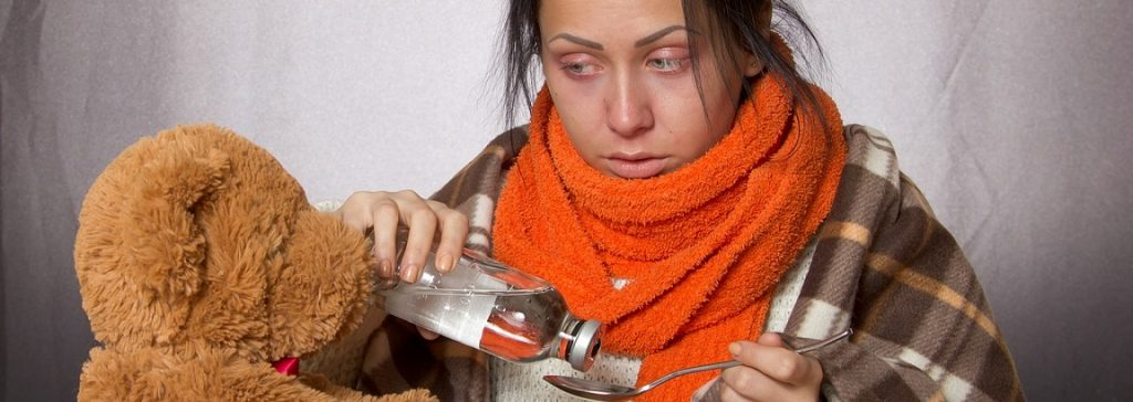 Woman wrapped up warm taking medicine